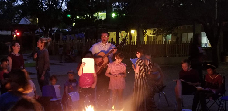Teacher David McNelly playing guitar around the campfire with students and families.