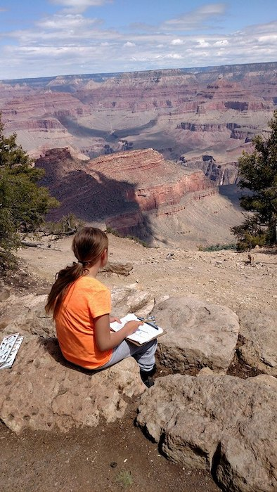 LTCS student sitting at the edge of the Grand Canyon with paper and pencil