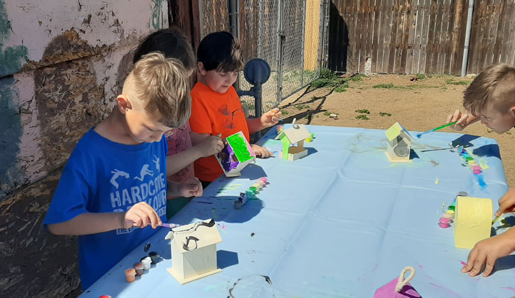 LTCS students painting bird houses outside in front of mural